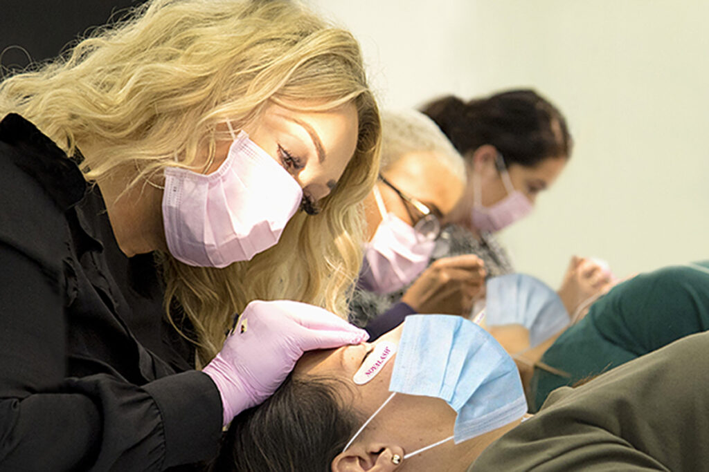 blond lady putting on eyelash extensions on lady